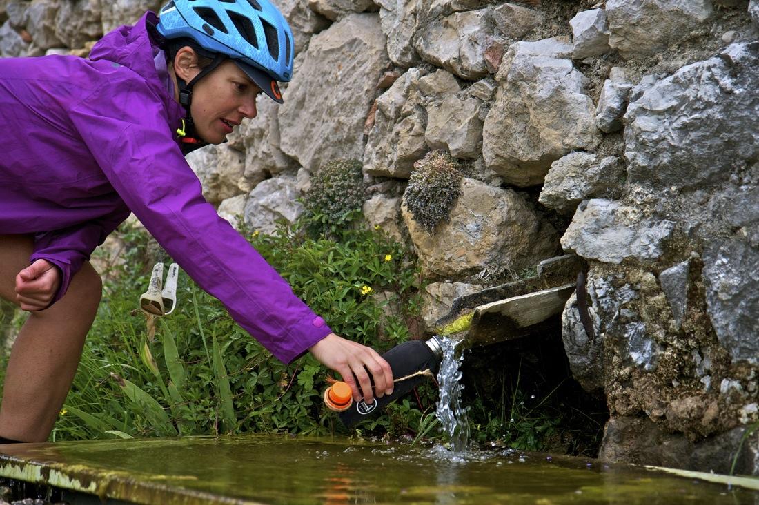 Fuente natural en el Catllaràs y ciclista. TransCatalunya Bikepacking.